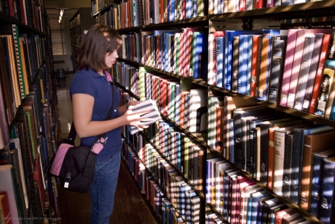 Woman looking at books from the library book shelf