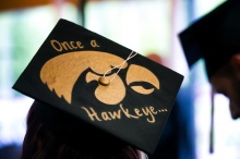 Top of a graduation cap with writing that says once a hawkeye...and has the herky profile logo in the middle