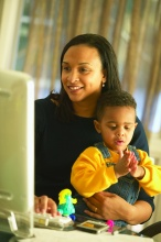 Smiling female student looking at a computer with child in her lap