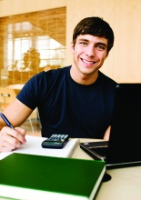 Smiling male student at desk writing